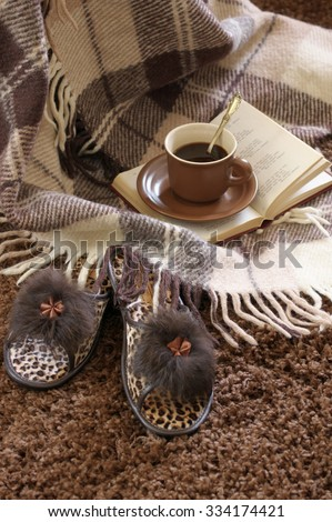 Woolen plaid, coffee cup, book and slippers on shaggy carpet.  - stock photo