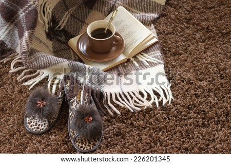 Woolen plaid, coffee cup, book and slippers on shaggy carpet. Focus on slippers. - stock photo