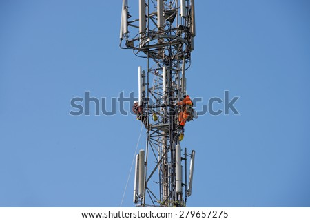 WORCESTER , ENGLAND -  APRIL 14 2015 : Maintenance men work high up a communications Tower - stock photo