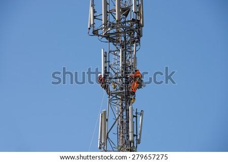 WORCESTER , ENGLAND -  APRIL 14 2015 : Maintenance men work high up a communications Tower - stock photo