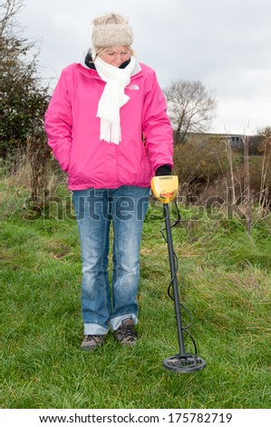 WORCESTER,UK-NOVEMBER 21 2010,A woman using a metal detector searching in a field.Metal detecting is a fast growing hobby - stock photo
