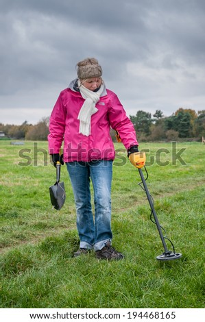 WORCESTER,UK-NOVEMBER 21 2010 :Woman with a metal detector searching in a field for buried metal. - stock photo