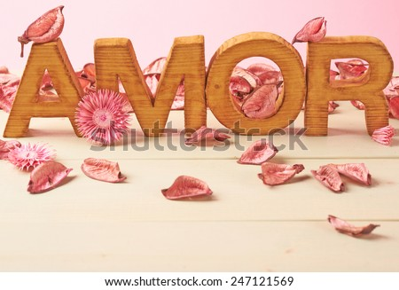 Word Amor meaning Love in multiple languages as a composition of wooden block letters covered with the dried flower potpourri leaves against the pink background - stock photo