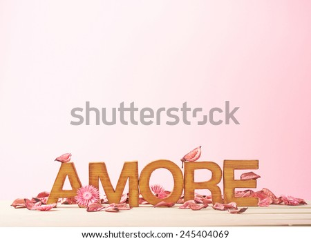 Word Amore meaning Love in Italian language as a composition of wooden block letters against the pink background - stock photo