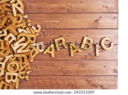 Word arabic made with block wooden letters next to a pile of other letters over the wooden board surface composition - stock photo