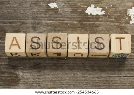 word assists on a wooden background - stock photo