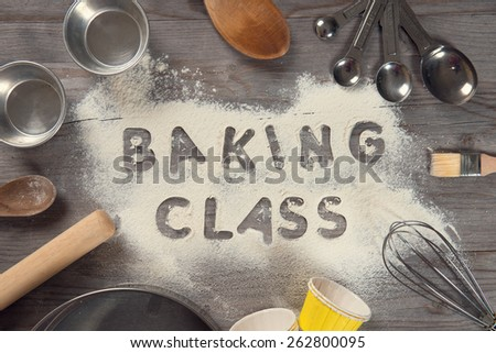 Word baking class written in white flour on a old wooden table from top view in vintage tone, surrounding by baking tools.  - stock photo