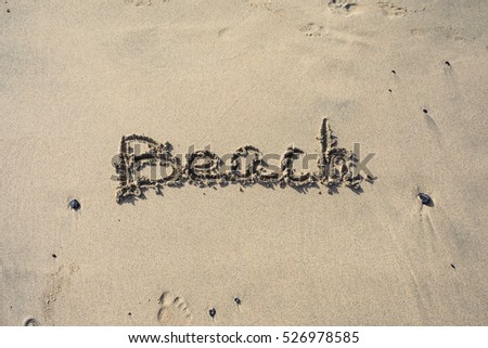 "Word ""Beach"" written on the sand. Concept of holidays. A lot of free space."