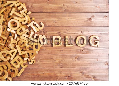 Word blog made with block wooden letters next to a pile of other letters over the wooden board surface composition - stock photo