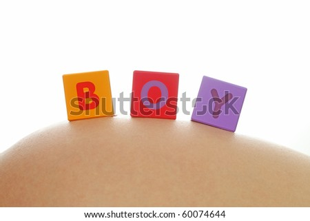 Word boy written with colorful alphabet cubes on pregnant belly - stock photo