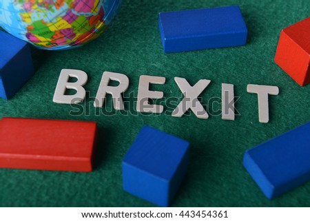 word BREXIT on green background with toy block and globe