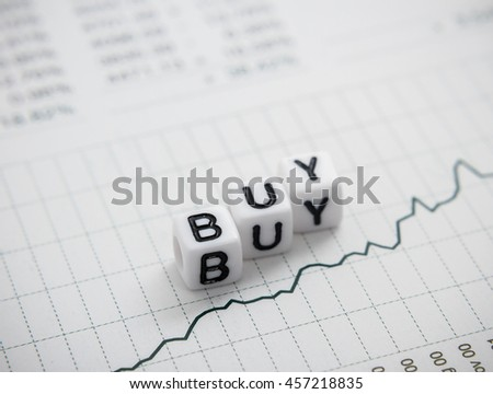 Word buy from letters cube on chart report, top view, soft focus