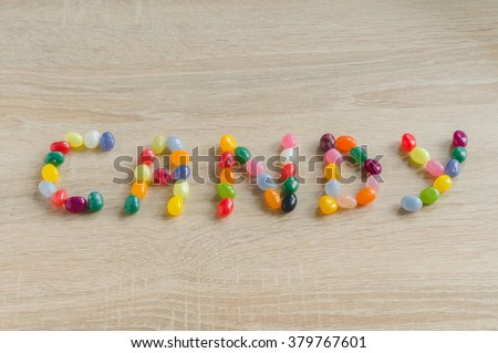 "Word ""candy"" from jelly beans on wooden background - stock photo"