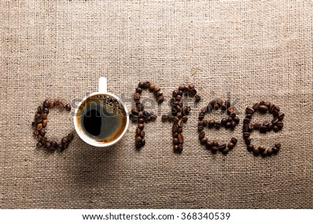Word COFFEE from coffee beans and cup on burlap background - stock photo