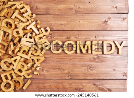 Word comedy made with block wooden letters next to a pile of other letters over the wooden board surface composition - stock photo