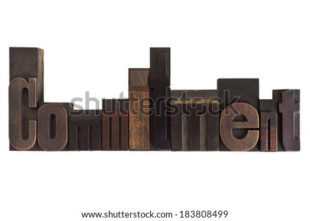 word commitment in vintage wooden letterpress type, scratched and stained, isolated on white background - stock photo