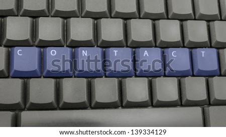 Word contact spelled with blue keys on computer keyboard.