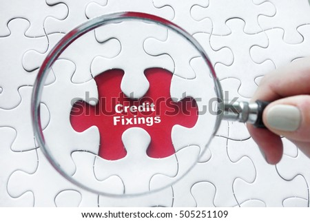 Word Credit Fixings with hand holding magnifying glass over jigsaw puzzle