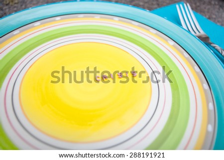 Word Crisis written with pasta on an empty colorful plate - stock photo