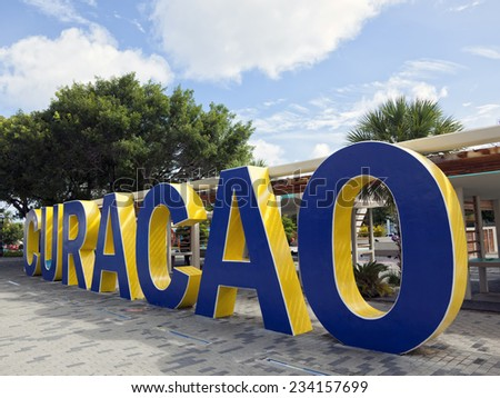 Word Curacao written in blue and yellow painted concrete letters at Queen Wilhelmina Park, Willemstad, Curacao - stock photo