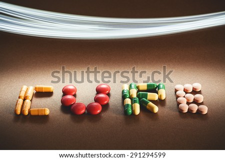 Word cure written with various different pills and tablets, lighting effect in upper side of image.  - stock photo