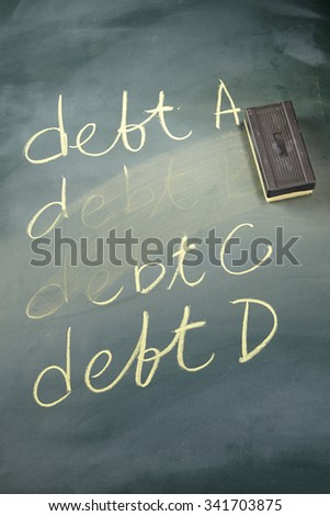 word DEBT written in chalk on a blackboard being rubbed out by an eraser - stock photo