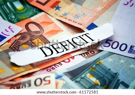 "Word ""Deficit"" printed on a piece of paper and placed above the pile of euro banknotes"