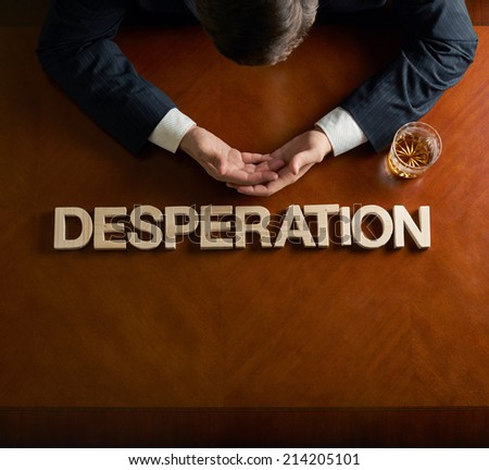 Word Desperation made of wooden block letters and devastated middle aged caucasian man in a black suit sitting at the table with the glass of whiskey, top view composition with dramatic lighting - stock photo