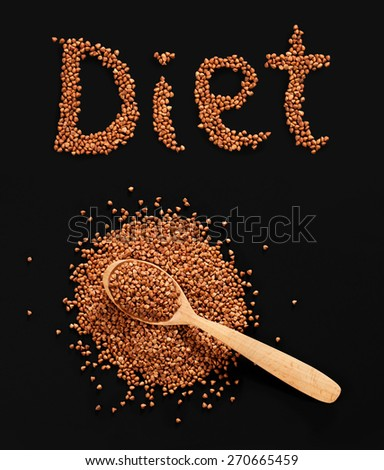 Word Diet composed of premium buckwheat groats on black background with wooden spoon - stock photo