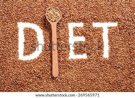 Word DIET composed on scattered buckwheat background with wooden spoon - stock photo