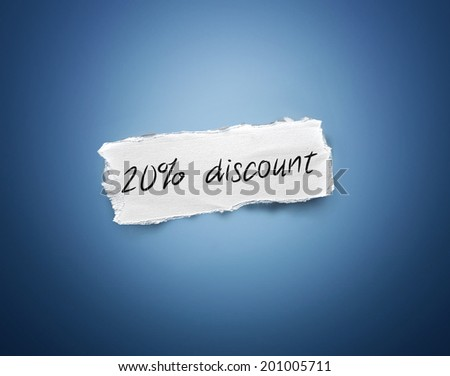 Word - 20% discount - written on a torn rectangular scrap of white paper on a blue background with a vignette - stock photo