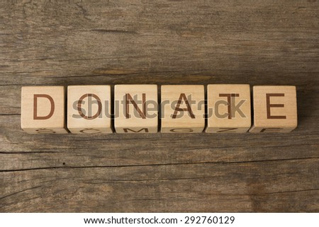 word DONATE on wooden cubes - stock photo