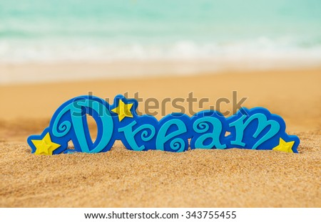 Word Dream on the sand beach - concept of  vacation and travel - stock photo