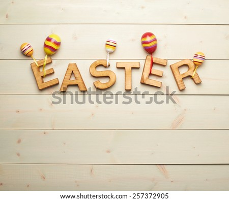 Word Easter made of wooden letters decorated with colorful toy eggs as a festive Easter background composition - stock photo