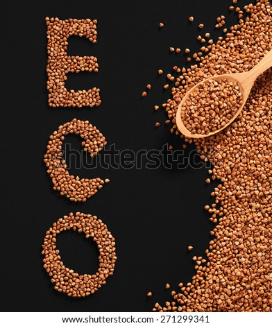 Word ECO composed of premium buckwheat groats on black background with wooden spoon - stock photo
