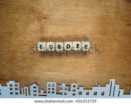 """Word """"Europe from the small cubes and the city cut out of paper on a wooden surface                                - stock photo"""
