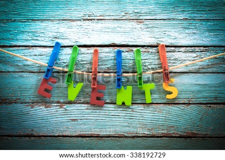word events fasten clothespins on a rope behind a wooden background - stock photo