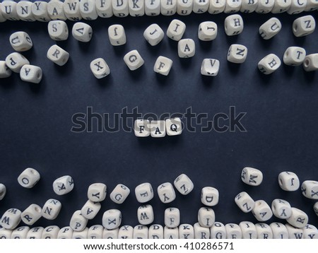 Word FAQ of small white cubes next to a bunch of other letters on the surface of the composition on a dark background                                - stock photo