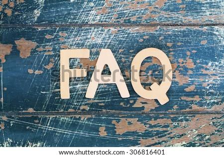 Word FAQ written on rustic wooden surface  - stock photo