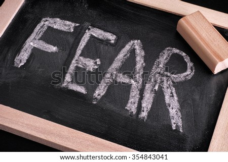Word Fear and eraser on chalkboard. Close up. - stock photo