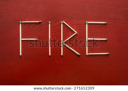 Word FIRE made of matchsticks green tip of sulfur isolated on red texture wooden background. Natural material Empty space for inscription  - stock photo