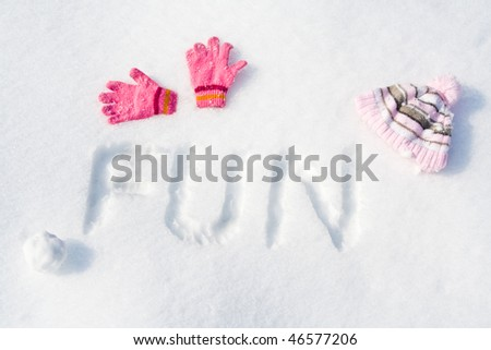 """Word """"FUN"""" written on fresh snow, with pink gloves, cap and snowball. - stock photo"""