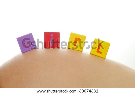Word girl written with colorful alphabet cubes on pregnant belly - stock photo