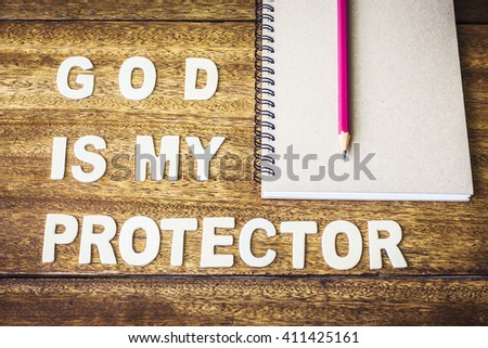 """word """" God is my protector"""" design by wooden letter press and small  notebook with red pencil on wooden background - stock photo"""