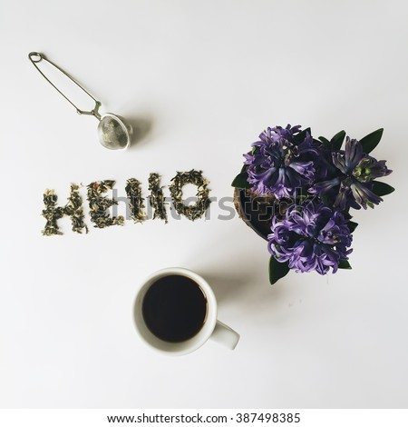 "Word ""Hello"" made with green tea, cup of tea and flowerpot with violet flowers. Isolated on white background. Overhead view. Flat lay, top view - stock photo"
