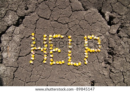 word HELP from grains of corn over cracked earth - stock photo