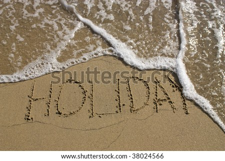 Word holiday written in the sandy beach. - stock photo