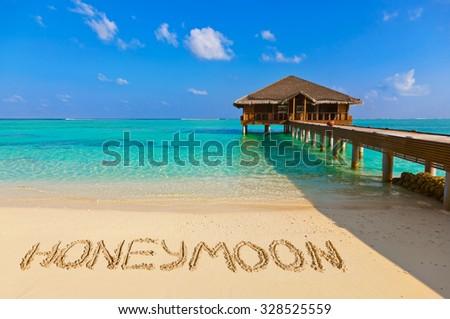 Word Honeymoon on beach - concept holiday background - stock photo