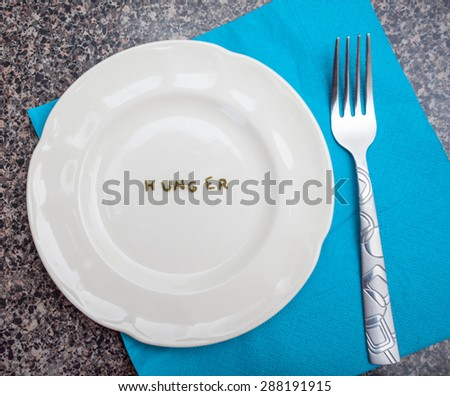 Word Hunger written with pasta on an empty white dish - stock photo