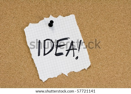 Word IDEA written on ripped paper on corkboard - stock photo